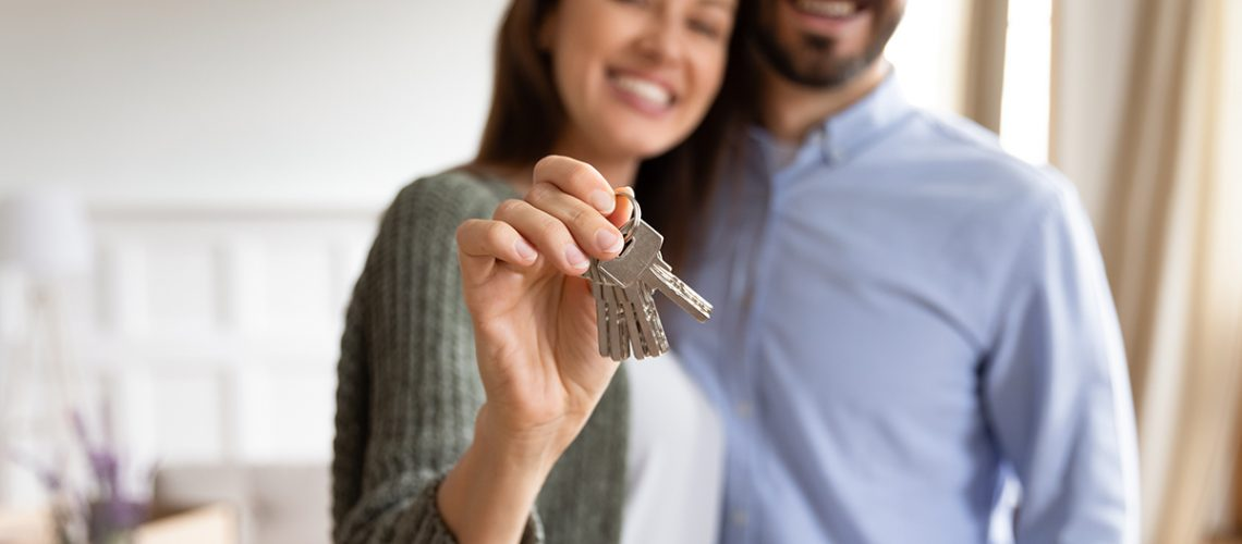 Smiling young couple hug hold show house keys feel overjoyed moving in to new apartment together, happy husband and wife embrace relocate to own shared home, real estate, ownership concept